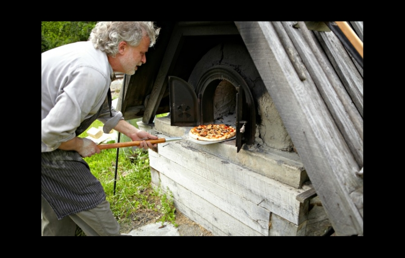 Scott Carrino makes artisan pizza by hand in community bread ovens at the Round House Bakery Cafe.